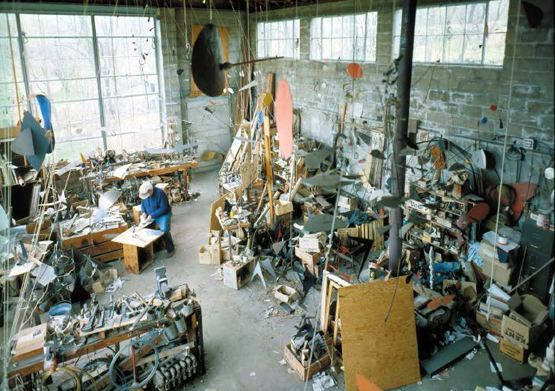 Alexander Calder in his shop with hanging mobiles, kinetic sculptures and materials